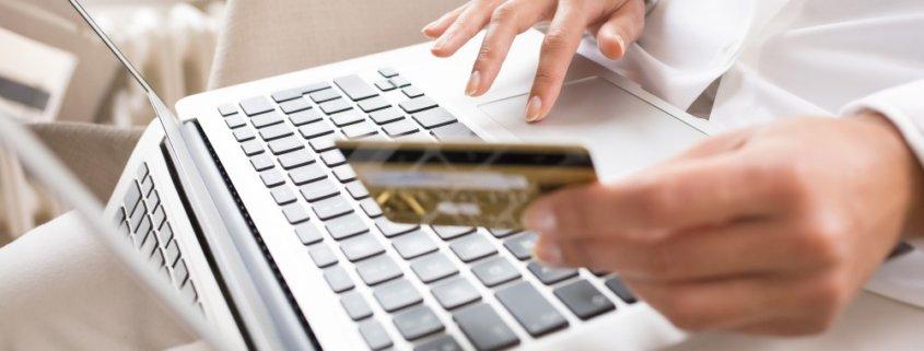 Kvinde ved computer med kreditkort i hånden